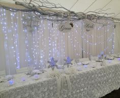 White wedding, winter wedding, winter wedding decor, winterwonderlandwedding , winter wonderland wedding decor, head table, lights, snowflakes, curly willow , bride and groom sign, twigs, rosett table linen, elegant wedding, fancy winter wedding, white and blue www.weddingrentalsonline.com