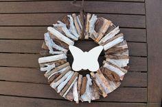 Türschmuck aus sommerlichen Hölzern mit Schmetterling in der Mitte.
