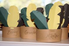 Native American headband place cards. Cut out feather shapes, position them on a strip of card stock and staple them together. Would go super cute with her Pilgrim hat place cards.