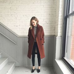 Gray turtleneck, black cropped skinny trousers, black loafers, rust double-breasted coat