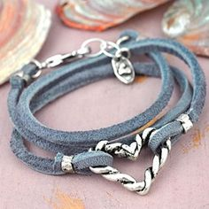 More twists than a mountain road! Grey leather lace wraps the wrist and features a heart of turned and twirled silver. Adjustable with a lobster claw closure accented with a fitting charm. brbrli...