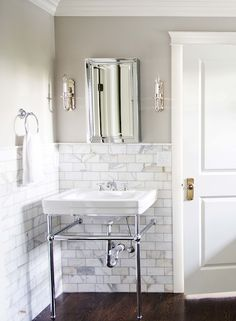 Stunning master bathroom with Benjamin Moore Revere Pewter on walls (a warm gray) and  calcutta gold marble subway tiles. Trim painted Benjamin Moore Intense White