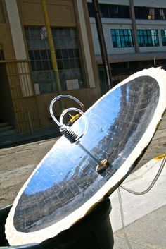 A solar water heater: a mirrored parabolic dish that focuses sunlight to a point, copper tubing that runs a thin stream of water through the very hot focal point, creating near-boiling water on-demand.