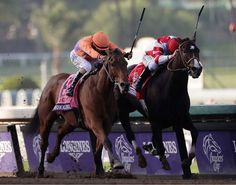 Beholder, left, with Gary Stevens, and Songbird, right, with Mike Smith, charge to the finish line in the Breeders