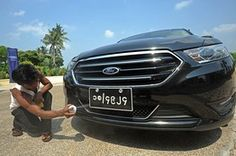 """""""A worker polishes a Ford during an event in Yangon announcing the American automaker's entry into Myanmar."""" From the Wall Street Journal: """"Ford Rolls Into Myanmar's Rusty Auto Market."""""""