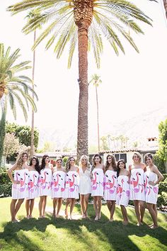 Modern palm springs wedding bride white dress getting ready before ceremony with bridesmaids in short pink flamingo robe dresses