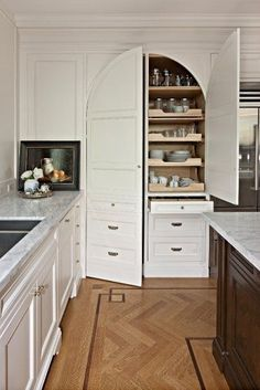 Beautiful traditional white painted kitchen pantry with arched doors, pantry next to corner, corner paneled to carry over crown molding details throughout the kitchen