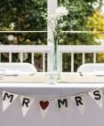 Mr. and Mrs. banner with simple centerpiece at head table.