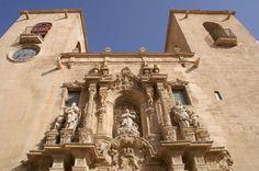 Iglesia de Santa María, Alicante.   En esta iglesia hallaremos la belleza interior de un templo gótico (s. XIV) que contrasta con el esplendor de su portada barroca y el altar mayor rococó, ambos del XVIII. Contemplemos también la pila bautismal (s. XVI) en mármol blanco de Carrara, el órgano, la rejería del XVIII y un incunable del XIII.