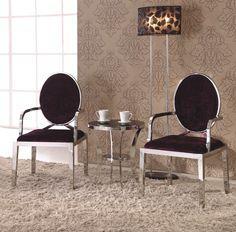 Chaise design au style baroque. La structure et ses accoudoirs sont en acier inoxydable et contrastent avec le tissu satiné de l'assise et du dossier. Le dossier capitonné en forme de médaillon lui apporte une touche de raffinement.