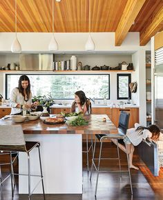 In the kitchen, designer Maca Huneeus prepares lunch with her daughters Ema, 12, and Ofelia, 7. The pendants are Jonathan Adler; the island is a custom design, inspired by a 1960s Dansk tray that belonged to Huneeus's mother.