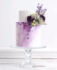 کیک زیبای جشن تولد یا سالگرد ازدواج تزیین شده با گل های طبیعی با تم سفید بنفش