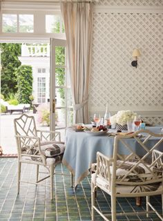 Suzanne McGrath Design - french doors with transom window, transom window,  distressed teal floors, floor to ceiling drapes, floor to ceiling curtains, oatmeal colored curtains, blue tablecloth, round table, brown and white palm frond seat cushions, wall sconce, trellis paneled walls, white trellis paneled walls,