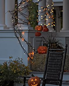 Prim Halloween...jack 'o lanterns & lighted twiggy branches and an old rocker.