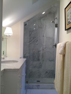 Art Exhibition Frameless glass door in marble shower with slanted ceiling