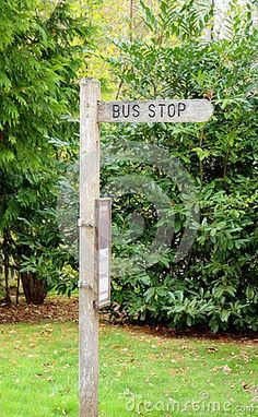 A wood bus stop sign on the countryside in Sussex.