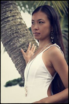 kanako dripping in adove fine jewelry. one of kind kahelelani and cone shell  earrings paired with polihale mother of pearl and gem kyanite splash necklace. made by dawn swimwear. photography by mami.