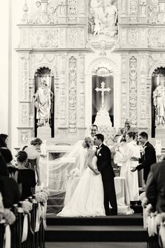 A full-skirted gown, grand church venue, and intimate hand holding make this traditional wedding kiss a showstopping image.