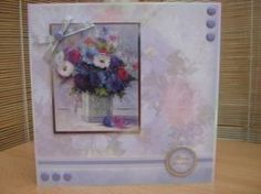 """This stunning card measures 8"""" x 8"""" in size and comes with a white envelope and protected in a cello bag. The topper features a beautiful display of flowers in a vase, has silver foiling around the edge and has been raised to give dimension. The sentiment reads """"Happy Birthday"""". Card Candi, and a silver bow have been added to decorate. The inside has been left blank for your own personal message…"""