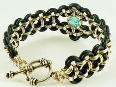 This completely unique Sterling silver and black rubber chainmail bracelet cuff is woven by alternating more than 212 rings of both kinds in double ring rows, highlighting a focal Aquamarine Swarovski crystal set in a customized chainmaille bezel configuration. Finished with a genuine