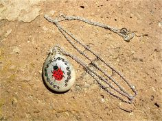 Ladybird lucky charm necklace ~ Vigil.  This necklace is a true gift passing on good luck and love: Features an intricate ladybird in red and black on a silver wash with a border of black swirls, hand-painted onto a natural beach pebble, then coated and sealed for durability.