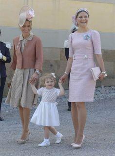 Estelle i vitt flankerad av mamma kronprinsessan Victoria och en av prinsessan Leonores faddrar, faster Tatjana d'Abo