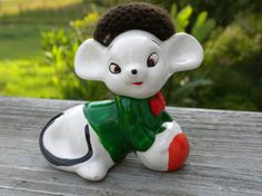This cute little white ceramic kitschy mouse figure is wearing a brown knitted hat, a green shirt and red bow tie. Measures:  3.5 inches long
