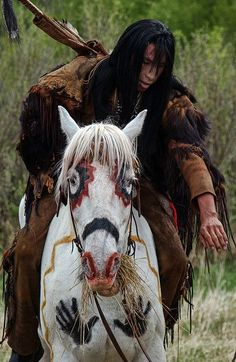 Native Am Indian riding horseback on a beautifully paint decorated horse. by shadowplay