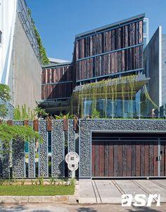 Tampilan depan rumah di siang hari. Unsur-unsur alam sangat mendominasi pada bagian fasad bangunan diantaranya aplikasi material kayu bekas, batu dan tanaman rambat.