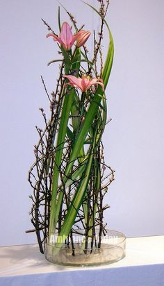 Cherry blossom armature encircling pink lilies and hala leaves