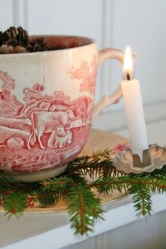 A tea cup is used with a bough of  greenery & a clip on candle for a vintage Christmas display.
