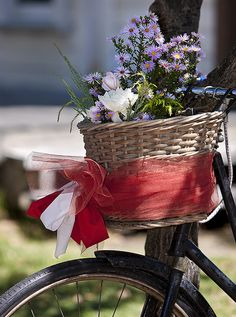 Flowers in the wicker basket on a bike with a large red ribbon tied around the basket