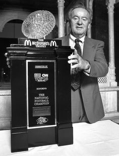 UW Head Football Coach Don James poses with the 1991 National Championship trophy after leading the Huskies to a 12-0 record and dismantling Michigan in the Rose Bowl.