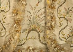 Detail embroidery, robe à l'anglaise (?), France, 1774-1793. White silk taffeta finely embroidered with a satin stitch floral in pastel silk, gold metallic thread and sequins, trimmed in silk gauze with leaf applique, back-lacing robe and boned bodice with a pair of triple stitched-down pleats at back, pleated skirt with curved waistline over hip, side openings and trained skirt, matching petticoat with scrolling floral and appliqued hem band.