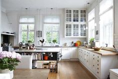 lots of light from the big windows with filmy shades. brightness expands in the white room with light shades of wood.