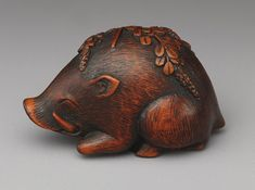 Boar resting on bush clover, nineteenth-century Japanese wooden netsuke. (Metropolitan Museum of Art)