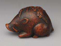 Boar resting on bush clover, nineteenth-century Japanese wooden netsuke. (Metropolitan Museum of Art)