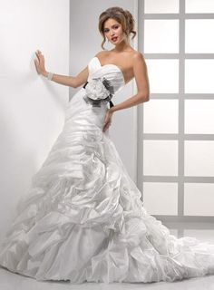 Bewildering romance is captured in this Vicenza Organza, dropped waist gown featuring sideswept bustles down the skirt and back train. A detachable belt with extravagant horsehair bow, handmade flowers, and Swarovski crystals convey modern luxury. Fitted A-line gown with sweetheart neckline and finished with a corset closure and bubble hem.