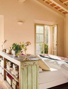 Rústico e vintage, o armário sem portas faz vez de cabeceira, apoio para a cama e criado-mudo, abrigando flores, luminárias e outros objetos.