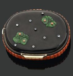 A rare and beautiful Art Deco compact by Cartier. Pebble-shaped black lacquer with gold accents, carved jade flowers, interspersed with coral and sapphires on the cover. Signed Cartier, Paris , London, New York.