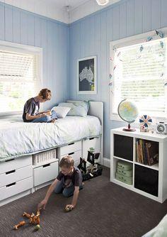 Bladoniebieska boazeria stanowi subtelne tło dla białych mebli w tym pokoju zaprojektowanym dla rodzeństwa. Dwa takie same łóżka zawierają dodatkowo szuflady do przechowywania ubrań, więc komody nie są już potrzebne. Szara wykładzina z ciekawą fakturą zapewnia wygodę podczas zabawy na podłodze.