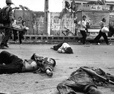 Street combat scene during the Tet Offensive, January 1968, Saigon. Two VC in the foreground, shot dead, one carrying an RPG, rocket unfired. Civilian casualty in the middle of the street. Civilians fleeing in the background.