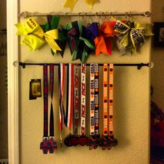 Cheer bow holder & medals holder. Used curtain rods and shower curtain hooks.