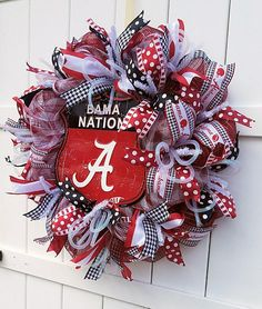Calling all Bama Nation fans! This is a handmade University of Alabama deco mesh wreath. The wreath is made with crimson and white deco mesh and adorned with coordinating ribbons. This wreath is made on a 24 inch work wreath. Perfect gift for any Alabama fan, new freshman, or