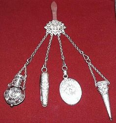French Silver Plated Chatelaine Featuring A Clip Medallion And Four Hanging Elements Consisting Of A Perfume Including A Small Glass Stopper, A Small Knife, A Covered Oval Mirror And A Scissors Holder With Each Having A Very Nice Fleur de Lis Decoration On The Front   c. 1880