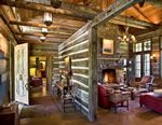 """Grey stain and wide chinking on the rough cut logs in this cozy log home.  The """"false"""" log wall is very clever in order to create a private foyer from the main great room"""
