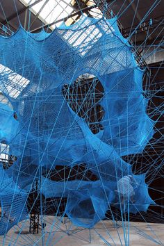 within the the carlswerk building in cologne, design collective numen/for use has constructed an immersive, tensile object made from stitched safety nets.