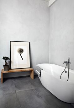 Simplicity. Minimalist grey bathroom. Love the wooden bench with oversided unhung Black & White print.