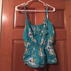 Floral tank top A floral tank top, with a blue back ground, there is a button up in the front. Forever 21 Tops Tank Tops
