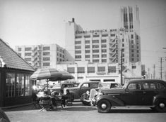 People sit under umbrellas by a small building that is mostly glass and roof in Boyle Heights, with the Sears looming behind them. 1938